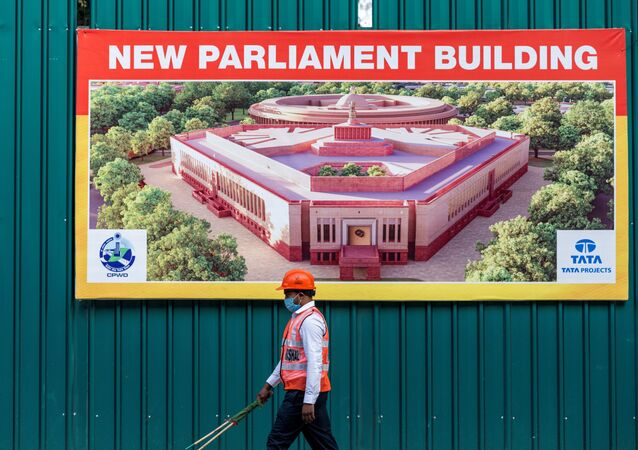 A worker walks past a banner at the boundary of the new Indian Parliament house construction site in New Delhi on December 10, 2020.