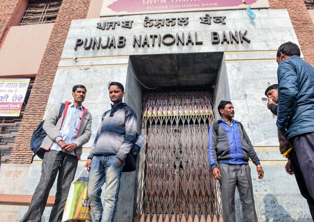 People look on as they stand in front of a closed outlet of Punjab National Bank during a nationwide bank strike in Amritsar on January 31, 2020