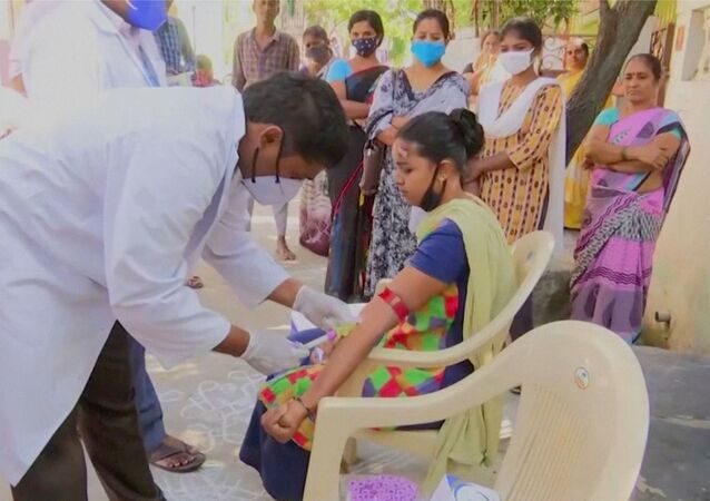 Healthcare personnel takes a blood sample from a patient during an examination, after hundreds of people were hospitalised due to an unknown illness in the southern state of Andhra Pradesh, in this still frame taken from video dated December 9, 2020