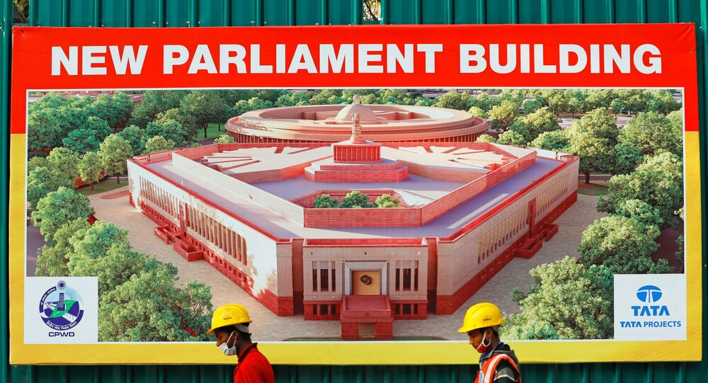 Construction workers walk past a hoarding featuring India's new parliament building outside its construction site in New Delhi, India, December 10, 2020.