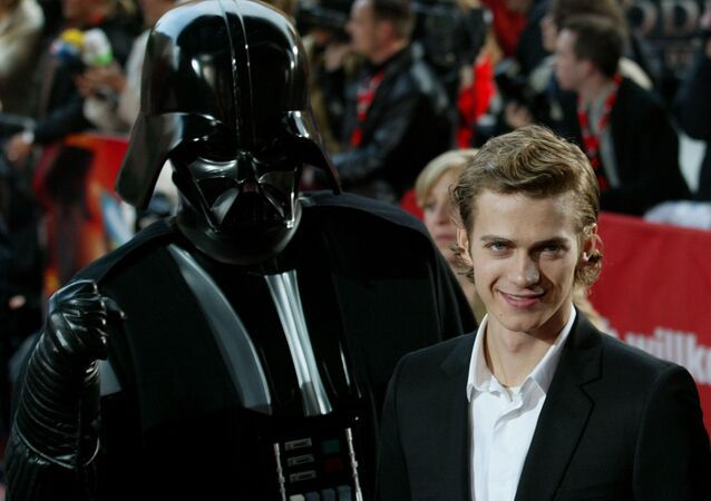 Actor Hayden Christensen poses next to a film character in front of a cinema at the Potsdamer Platz square in Berlin on Tuesday, May 17, 2005