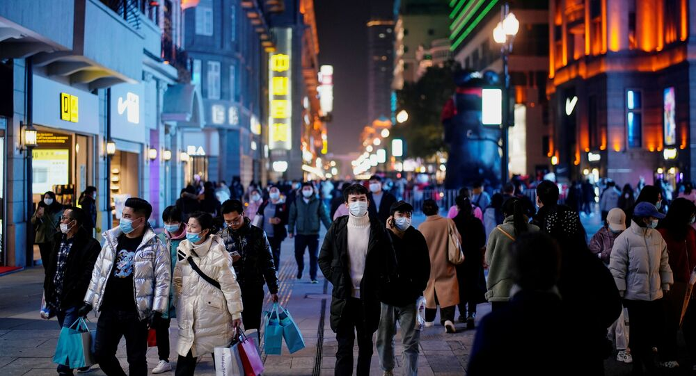 People wearing face masks are seen at a main shopping area almost a year after the global outbreak of the coronavirus disease (COVID-19) in Wuhan, Hubei province, China December 7, 2020. Picture taken December 7, 2020