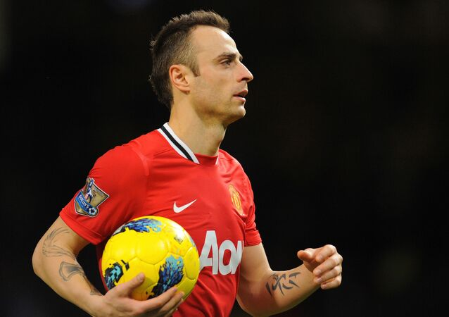 Manchester United's Bulgarian striker Dimitar Berbatov leaves the pitch with the match ball after scoring a hat trick during the English Premier League football match between Manchester United and Wigan Athletic at Old Trafford in Manchester, north-west England on December 26, 2011