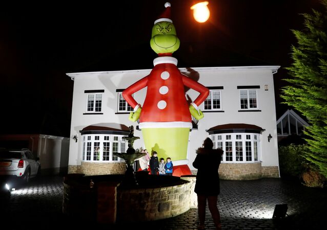 People pose in front of a giant inflatable character The Grinch outside a house, amid the outbreak of the coronavirus disease (COVID-19) in Hartlepool, Britan November 29, 2020.