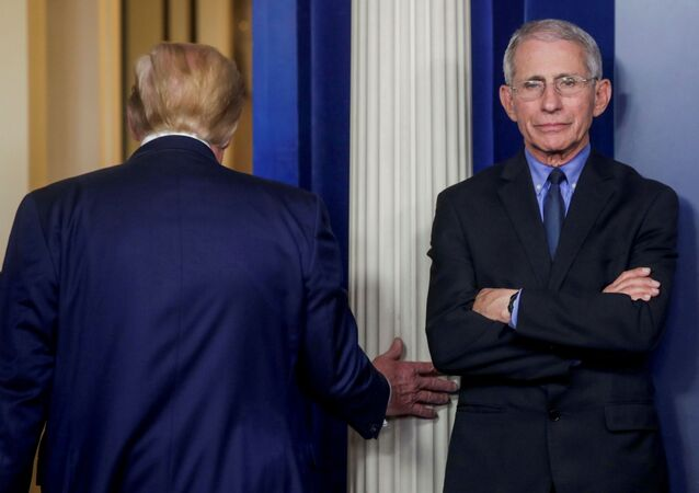 US President Donald Trump departs after addressing the coronavirus task force daily briefing as Dr. Anthony Fauci, director of the National Institute of Allergy and Infectious Diseases, stands by at the White House in Washington, 26 March 2020.