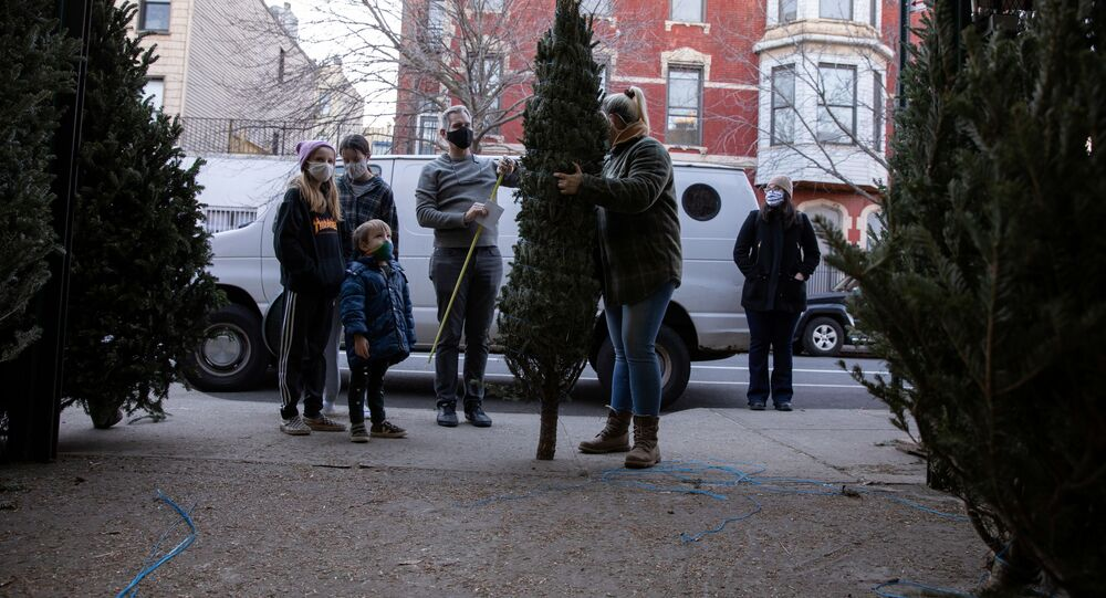 Doug Hassebroek inspects a potential Christmas tree with his family, as the global outbreak of the coronavirus disease (COVID-19) continues, in Brooklyn, New York, U.S., December 6, 2020.