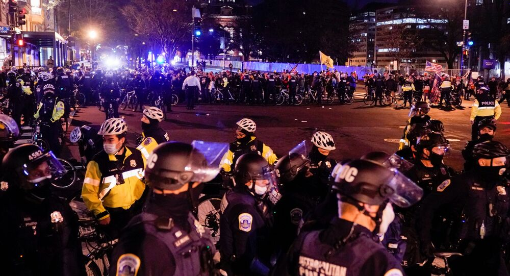 Police officers stand in formation to separate members of the Proud Boys group and counter protesters, in downtown Washington, U.S., 12 December 2020.