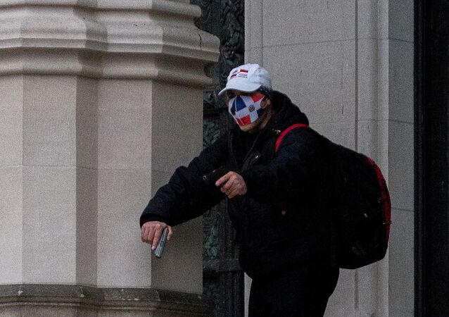 A man wearing a protective mask points his guns outside the Cathedral Church of St. John the Divine in the Manhattan borough of New York City, New York, U.S., December 13, 2020