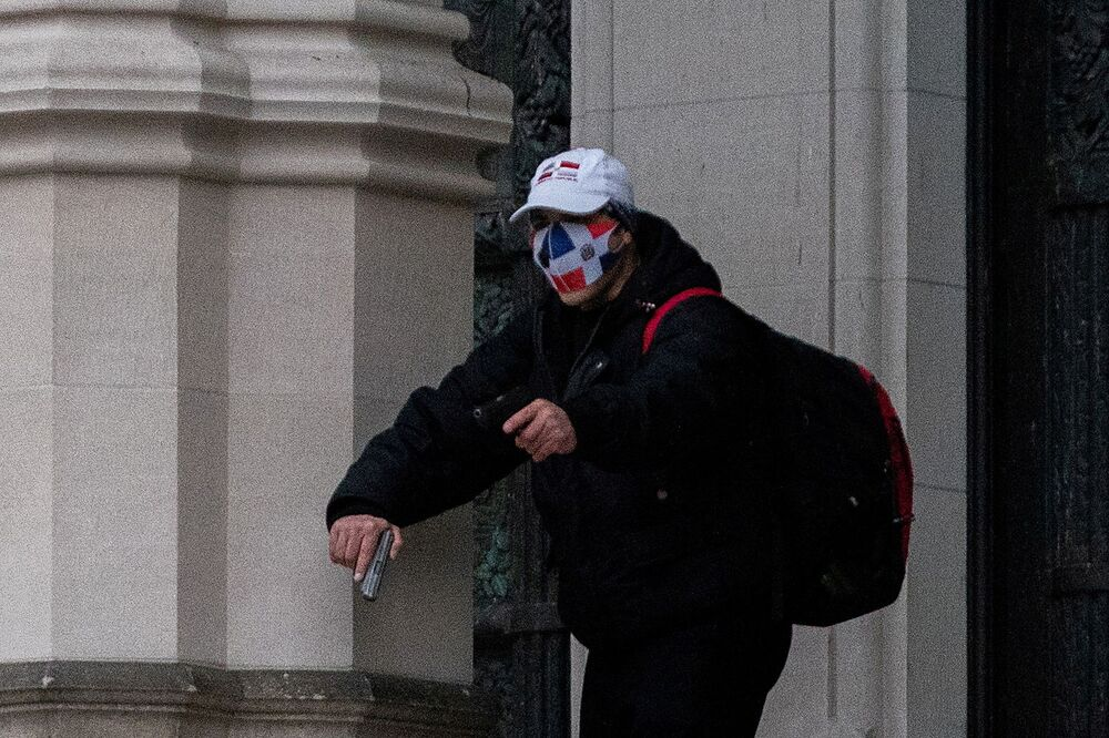 A man wearing a protective mask points his gun outside the Cathedral Church of St. John the Divine in the Manhattan borough of New York City, New York, U.S., December 13, 2020.