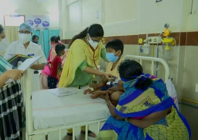 A doctor examines a young patient lying in a hospital bed at an Eluru hospital, after hundreds of people were hospitalised due to an unknown illness in the southern state of Andhra Pradesh, in this still frame taken from video dated December 9, 2020