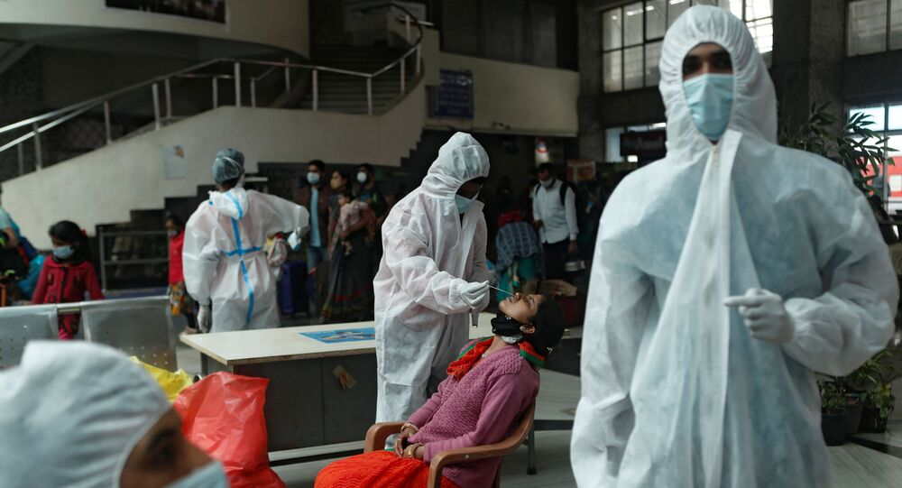 A health worker in personal protective equipment (PPE) collects a swab sample from a woman during a rapid antigen testing campaign for the coronavirus disease (COVID-19), at a railway station in Mumbai, India, December 11, 2020