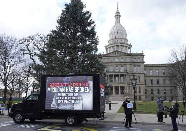 Motorist's participate during a drive-by rally to certify the presidential election results near the Capitol building in Lansing, Mich., Saturday, Nov. 14, 2020