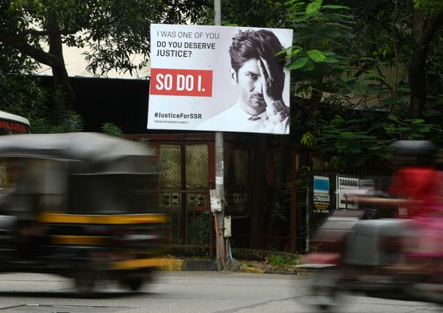 Vehicles drive past a hoarding put up to seek justice following the suicide of actor Sushant Singh Rajput, in Mumbai on September 28, 2020
