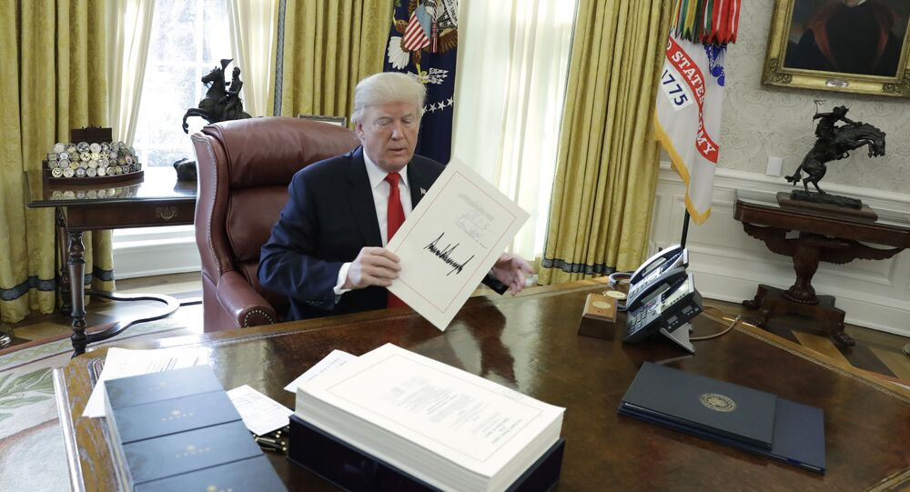 President Donald Trump displays the $1.5 trillion tax overhaul package he had just signed, Friday, Dec. 22, 2017, in the Oval Office of the White House in Washington. The bill provides generous tax cuts for corporations and the wealthiest Americans, plus smaller cuts for middle- and low-income families.