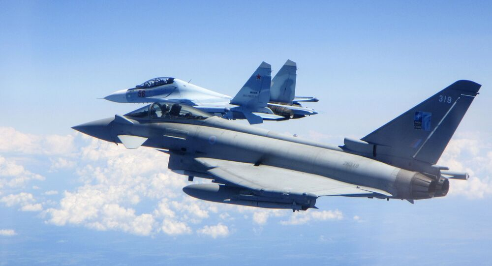 In this photo taken on Saturday, June 15, 2019, a Royal Air Force Typhoon jet, foreground, flies by a Su-30 Flanker fighter.