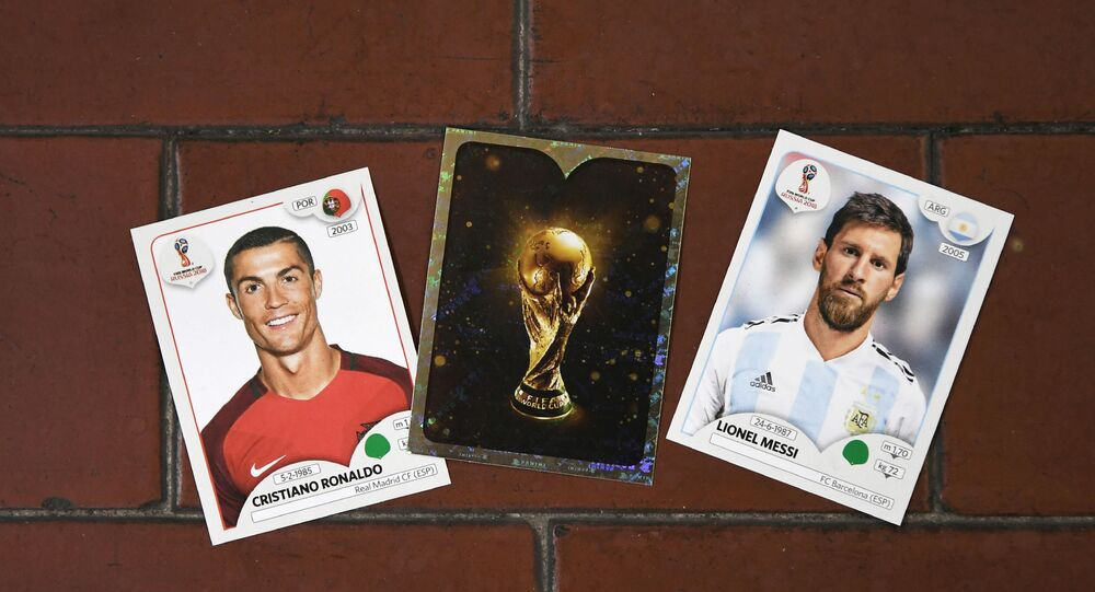 This photo taken on April 20, 2018 shows collectible cards featuring (L-R) Portugal's forward Cristiano Ronaldo, the Fifa World Cup Trophy and Argentina's forward Lionel Messi as part of a series featuring players for the 2018 Russia football World Cup at the Panini Group factory in Modena, northern Italy.