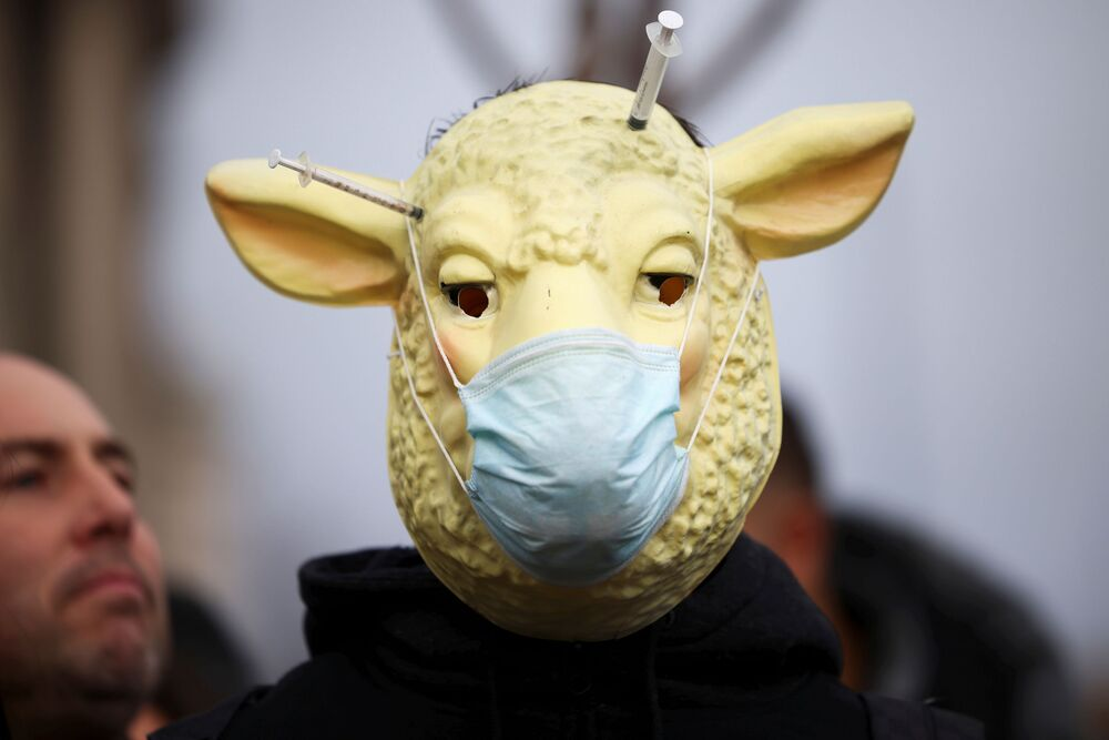 A person with a lamb mask participates in an anti-vaccination demonstration at the Parliament Square in London, Britain, 14 December 2020.