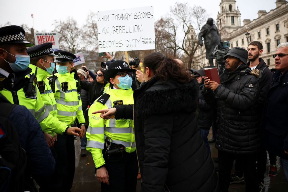 A woman talks with police officers during an anti-vaccination demonstration at the Parliament Square in London, Britain, 14 December 2020.