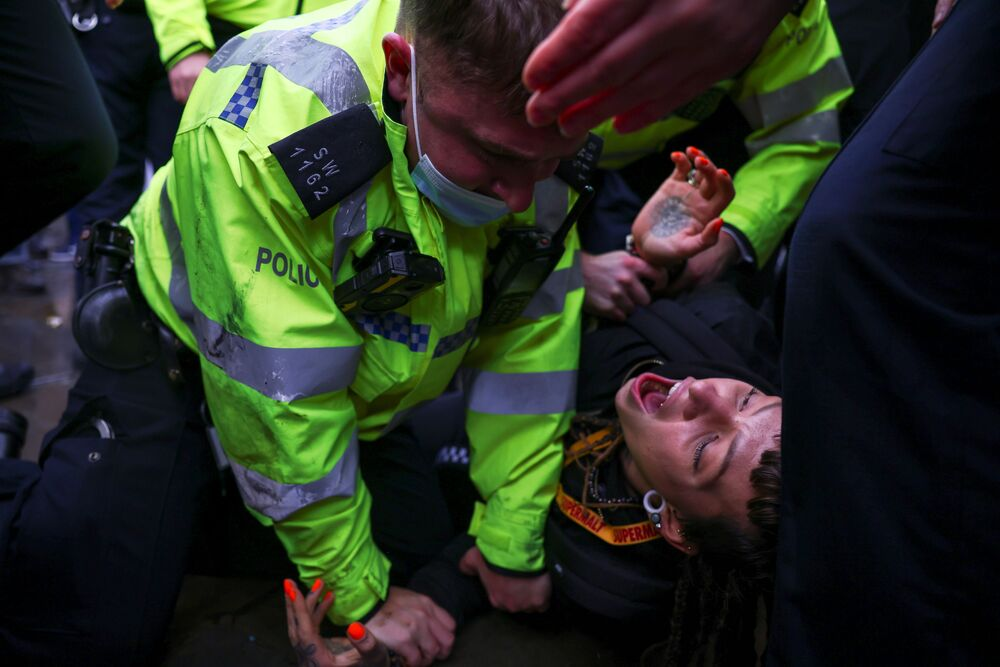 A demonstrator is detained by police officers during an anti-vaccination demonstration at the Parliament Square in London, Britain, 14 December 2020.