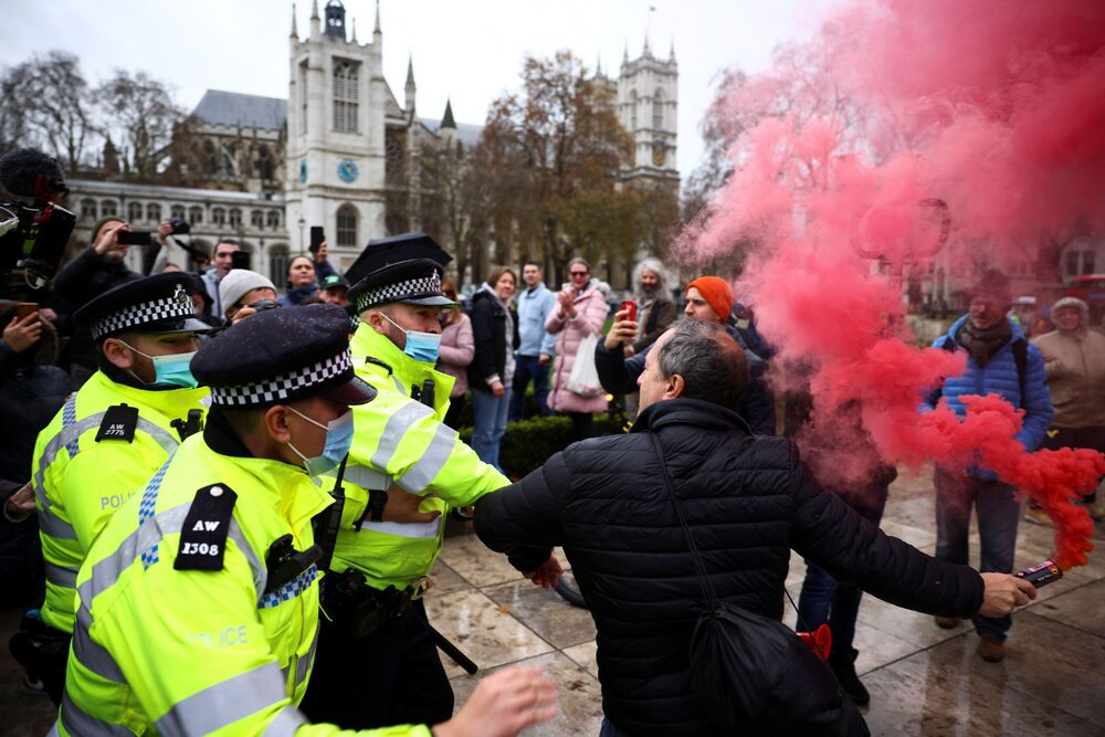 A man struggles with police officers during an anti-vaccination demonstration at the Parliament Square in London, Britain, 14 December 2020.