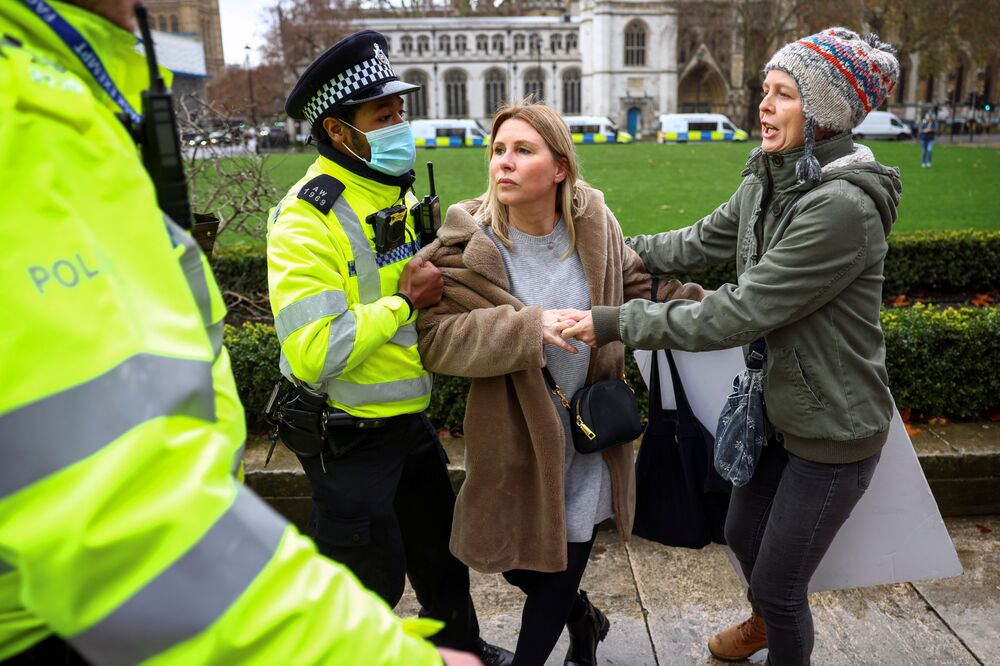 A police officer tries to detain an anti-vaccination activist as another protester tries to release her during an anti-vaccination demonstration at the Parliament Square in London, Britain 14 December 2020.