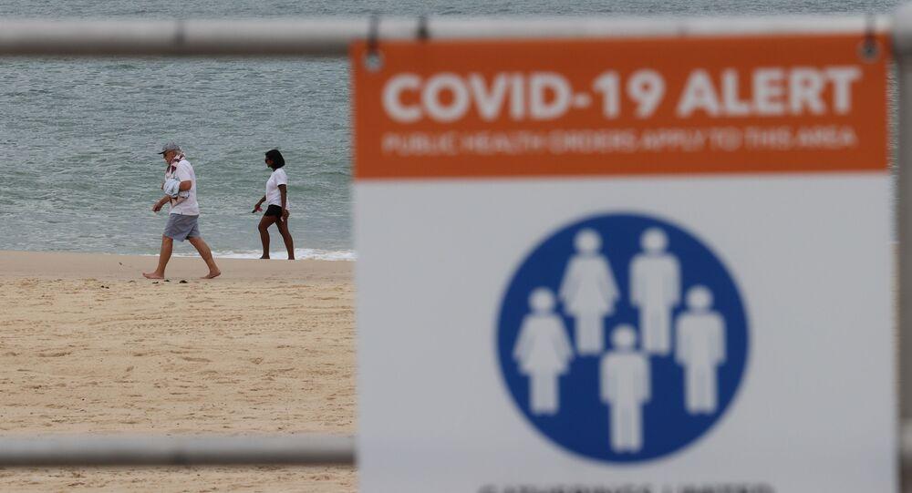 People walk by the ocean beyond a coronavirus disease (COVID-19) public health warning sign at Bondi Beach in Sydney, Australia, November 23, 2020
