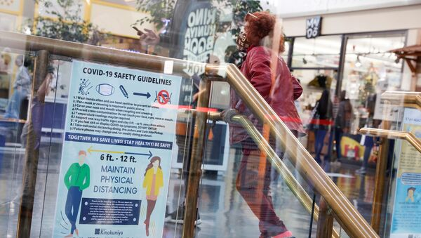 A masked customer ascends a flight of stairs inside Japan Center in Japantown ahead of the new stay-at-home order in attempts to contain the spread of the coronavirus disease (COVID-19) in San Francisco, California, U.S., December 6, 2020 - Sputnik International
