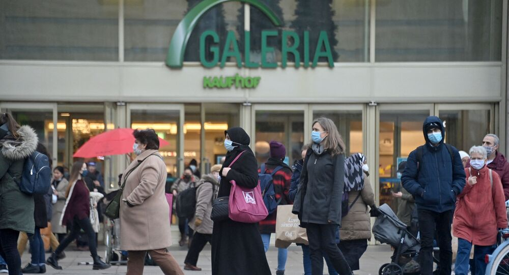 Shoppers and pedestrians wearing face masks walk across Alexanderplatz in front of the Galeria Kaufhaus department store in the centre of Berlin on December 14, 2020, a few days ahead of a partial lockdown to curb the spread of the ongoing novel coronavirus (Covid-19) pandemic.