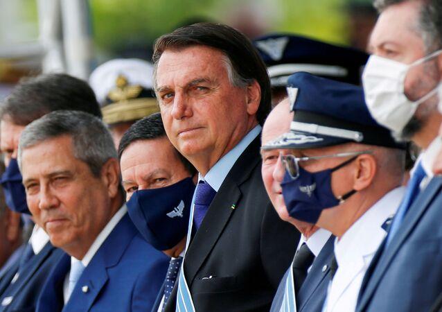 Brazil's President Jair Bolsonaro (C) looks on during a ceremony of Aviator's Day at Brasilia Air Base in Brasilia, Brazil 23 October, 2020.