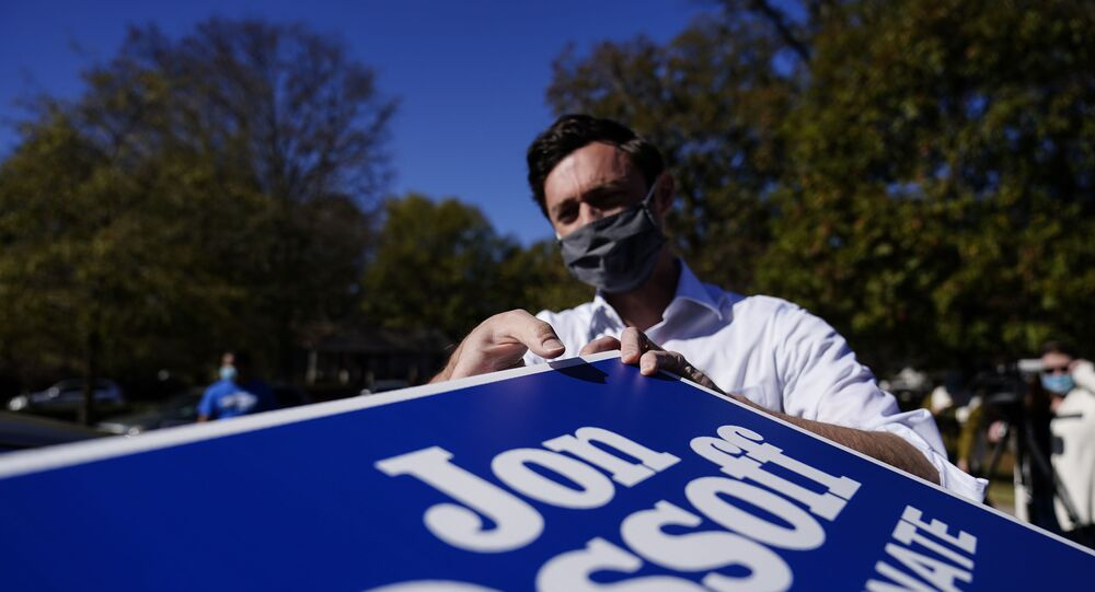 Georgia Democratic candidate for U.S. Senate Jon Ossoff grabs signs to give out during a drive-through yard sign pick-up event on Wednesday, Nov. 18, 2020, in Marietta, Ga. Ossoff and Republican candidate for Senate Sen. David Perdue are in a runoff election for the Senate seat.