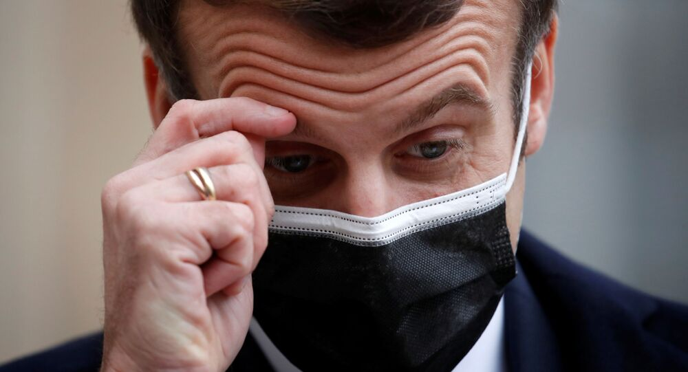 French President Emmanuel Macron, wearing a protective face mask, scratches his brow as he talks to the media next to Portugal's Prime Minister Antonio Costa (not seen) before a meeting at the Elysee Palace in Paris, France, 16 December 2020