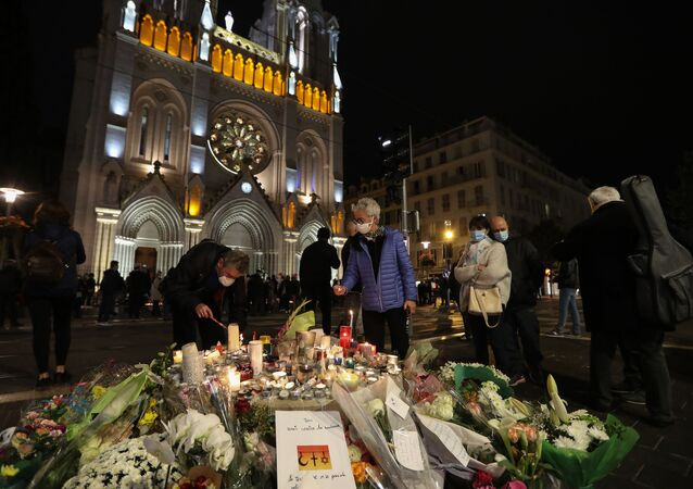 People light candles outside Notre-Dame de l'Assomption Basilica in Nice on October 31, 2020, to pay tribute to the victims two days after a knife attacker killed three people, cutting the throat of two, inside the church of the French Riviera city, and police arrest a young Tunisian migrant from Sfax who arrived in Europe only last month, according to French prosecutors.