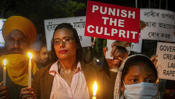Indians hold placards protesting against the alleged gang rape and killing of a Dalit woman in Uttar Pradesh state, in Gauhati, India, Saturday, Oct. 10, 2020 - Sputnik International