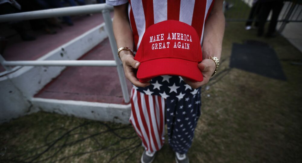 A man dressed in American flag clothes holds Make America Great Again hats before President-elect Donald Trump speaks at a rally at the Ladd–Peebles Stadium, Saturday, Dec. 17, 2016, in Mobile, Ala