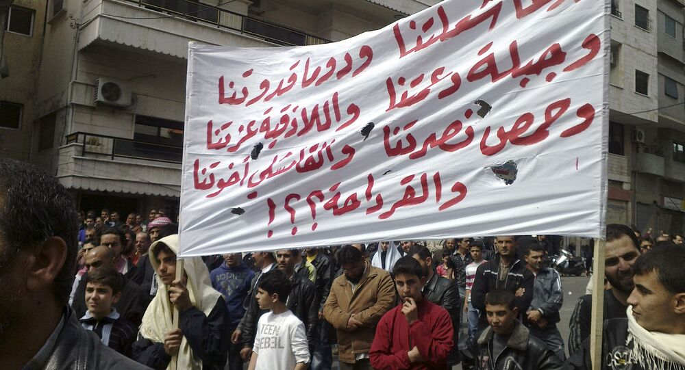 In this citizen journalism image made on a mobile phone and acquired by the AP, Syrian anti-government protesters carry a banner in Arabic that reads: Daraa is our torch, Douma is our model, Jabla is our support, Latakia is our pride, Homs is our victory, in Qamishli our brothers and what about Qardaha ??!, knowing that Qardaha is the home village of Syrian President Bashar Assad, as they gather in the coastal city of Banias, Syria, Friday, April 22, 2011