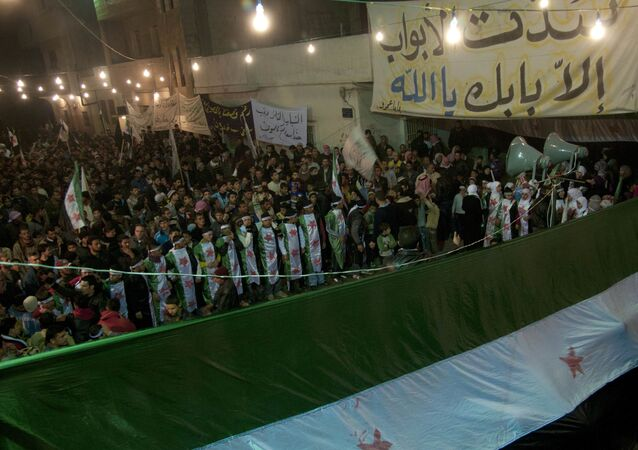 In this photo taken on Wednesday Dec. 21, 2011, anti-Syrian regime protesters, some wearing Syrian revolution flags, gather during a night demonstration in the Baba Amr area, in Homs province, Syria