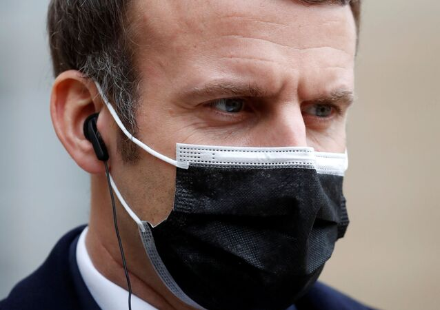French President Emmanuel Macron, wearing a protective face mask, listens to Portugal's Prime Minister Antonio Costa (not seen) as they talk to the media before a meeting at the Elysee Palace in Paris, France, December 16, 2020