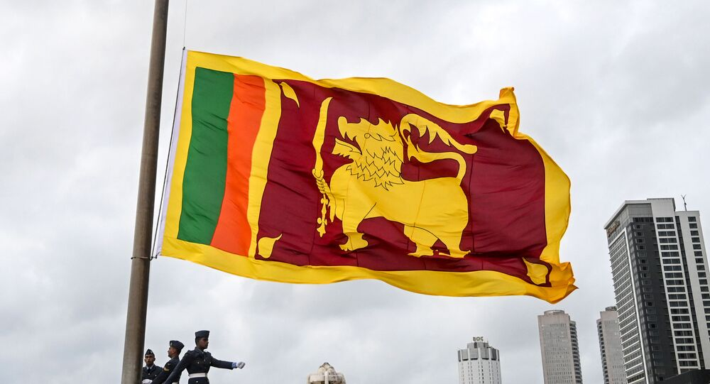 Soldiers stand at attention as the national flag is lowered as part of a daily ceremony at the Galle Face Green promenade in Colombo on May 17, 2020.