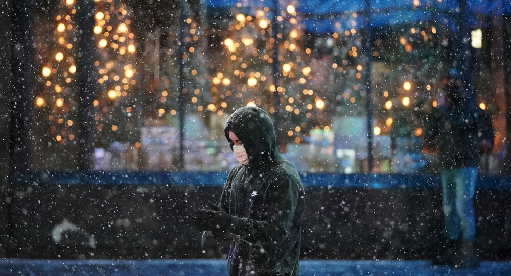 A person wearing a protective face mask walks as snow begins to fall in Times Square during a Nor'easter, during the coronavirus disease (COVID-19) pandemic in the Manhattan borough of New York City, New York, U.S., December 16, 2020