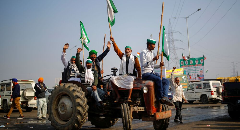 Farmers shout slogans as they sit on a tractor during a protest against farm bills passed by India's parliament, at the Delhi-Uttar Pradesh border in Ghaziabad, India, December 16, 2020