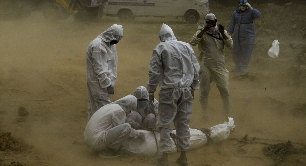 Relatives wearing protective gear tie up the dead body  before the burial at a graveyard in New Delhi (File)
