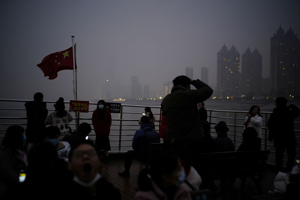 People wearing face masks take a ferry as they pass the Yangtze River at dusk almost a year after the global outbreak of the coronavirus disease (COVID-19) in Wuhan, Hubei Province, China, 11 December 2020.