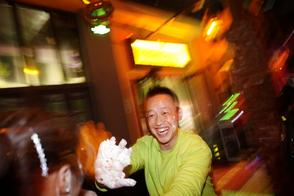 People put cream from a birthday cake on each other at a bar almost a year after the global outbreak of the coronavirus disease (COVID-19) in Wuhan, Hubei Province, China, 11 December 2020.