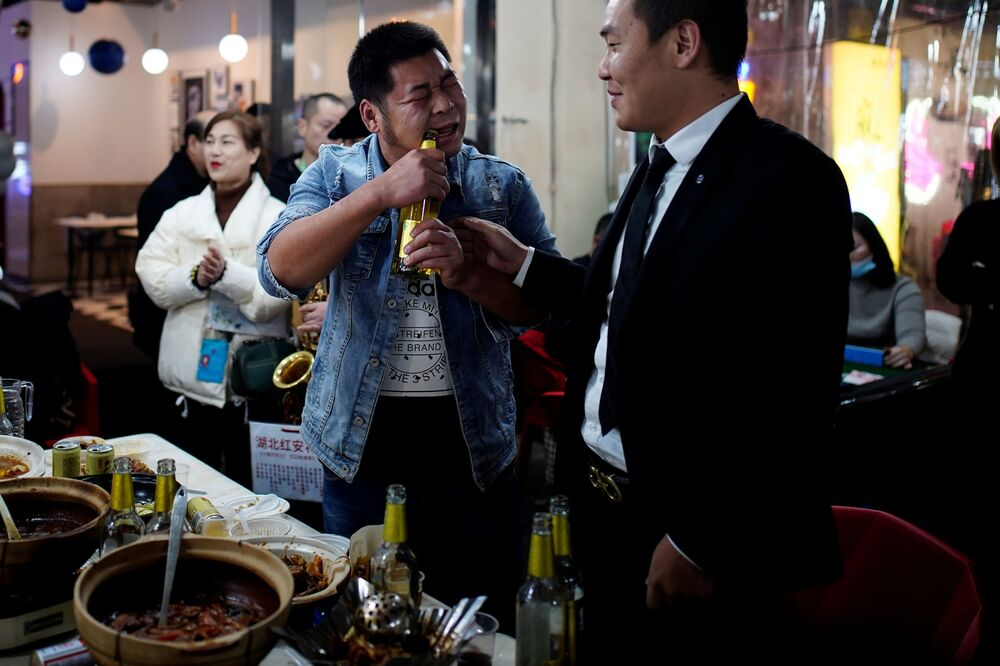 A man opens a bottle of beer with his teeth at a street restaurant almost a year after the global outbreak of the coronavirus disease (COVID-19) in Wuhan, Hubei Province, China, 11 December 2020.