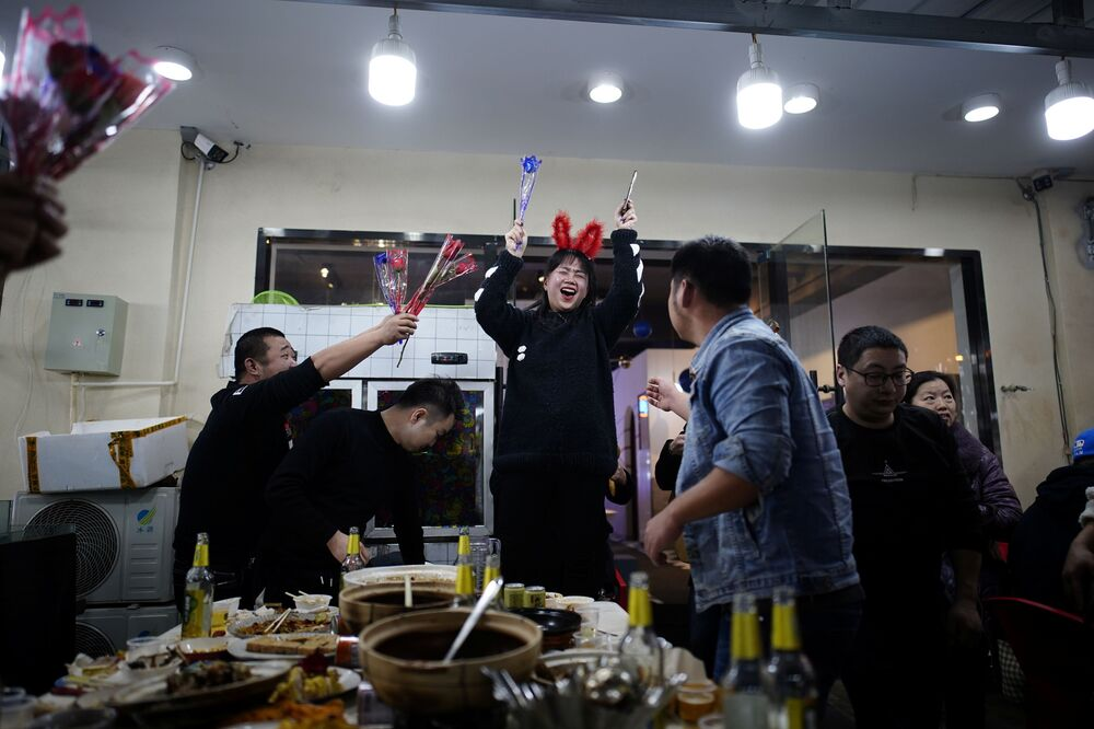 People celebrate a birthday at a street restaurant almost a year after the global outbreak of the coronavirus disease (COVID-19) in Wuhan, Hubei Province, China, 11 December 2020.