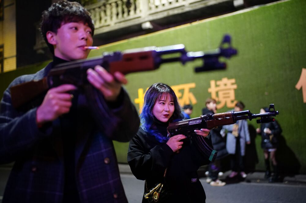 People play with toy guns outside a bar at night almost a year after the global outbreak of the coronavirus disease (COVID-19) in Wuhan, Hubei Province, China, 11 December 2020.