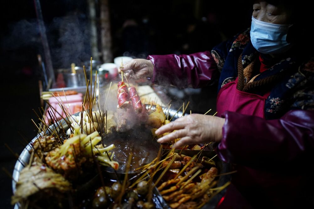 A snack vendor sells snacks outside a bar on a street almost a year after the global outbreak of the coronavirus disease (COVID-19) in Wuhan, Hubei Province, China, 11 December 2020.