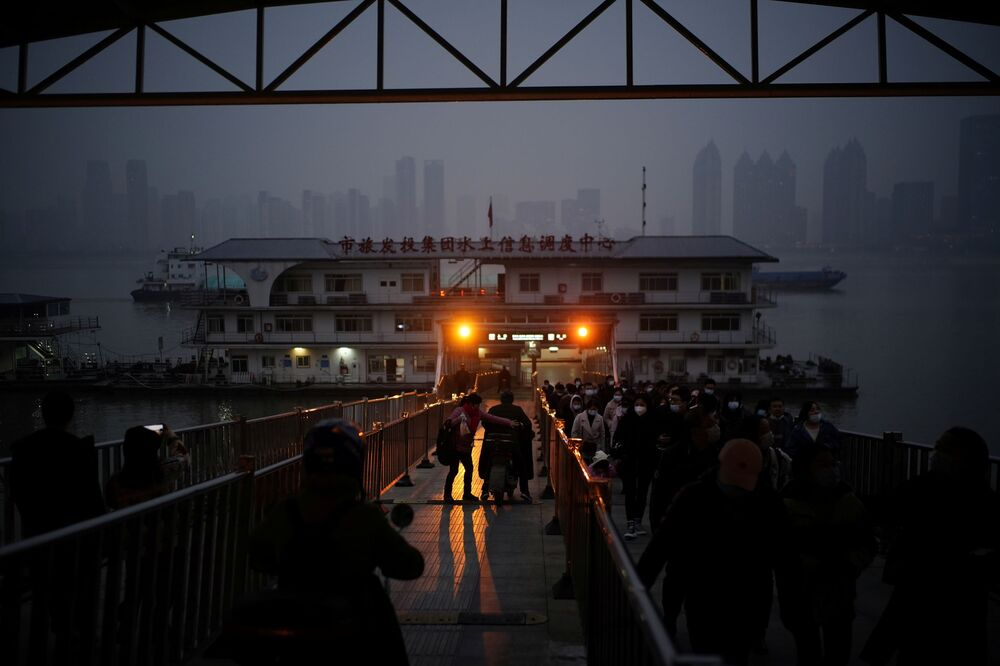 People wearing face masks walk out of a ferry as they pass the Yangtze River at dusk almost a year after the global outbreak of the coronavirus disease (COVID-19) in Wuhan, Hubei Province, China, 11 December 2020.