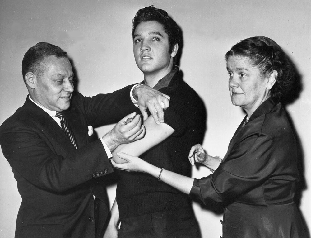 Elvis Presley receives a Salk polio vaccine shot from Dr. Harold Fuerst on  28 October, 1956, in New York City.