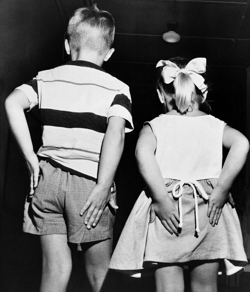 Coggie Pearce, left, and his sister, Debbie, 4, rub their behinds after receiving inoculations of gamma globulin in mass testing of the preventative polio vaccine, 2 July, 1952.